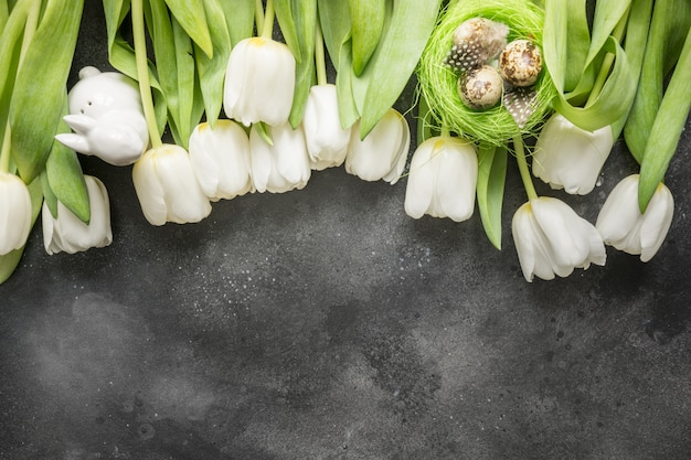 Easter pattern. border of white tulips, eggs, nest on vintage gray. top view with copy space.