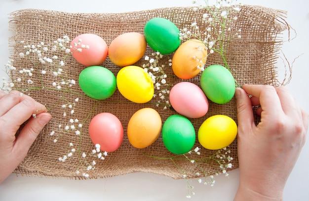 白い背景に花とキャンディーと卵のイースターパターンイースターの概念健康的な摂食の概念