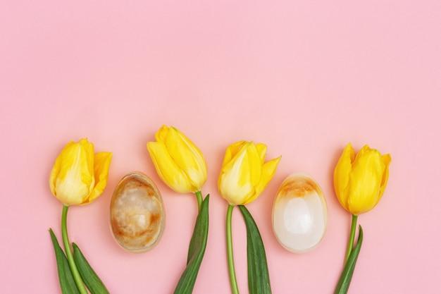 튤립의 노란색 꽃과 돌 질감으로 계란 부활절 패턴