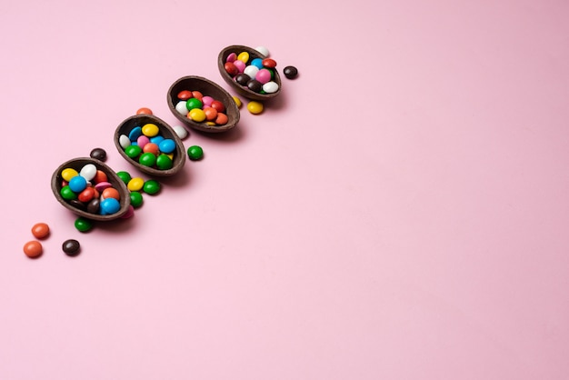 Easter pink background with multi-colored candy in a chocolate nest - copyspace