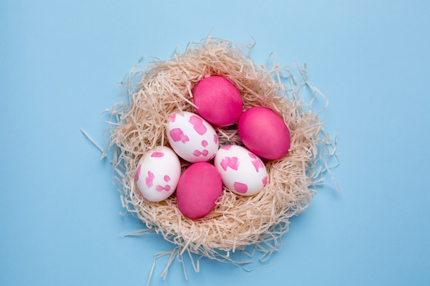 Easter pink eggs with watercolor brushstrokes on a blue surface