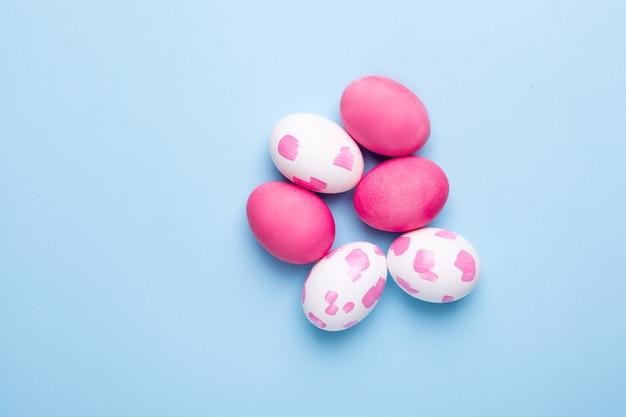 青い表面に水彩筆でピンクのイースターエッグ