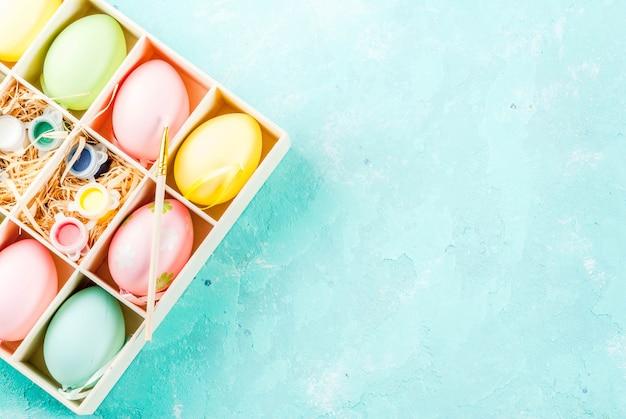 イースター、休日の準備。卵、ペイント、木製のボックス、ライトブルー、トップビューで着色用ブラシ
