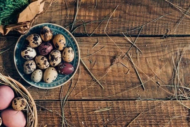 부활절 준비. 접시에 있는 부활절 달걀과 건초가 있는 소박한 나무 테이블에 누워 있는 식물의 상위 뷰