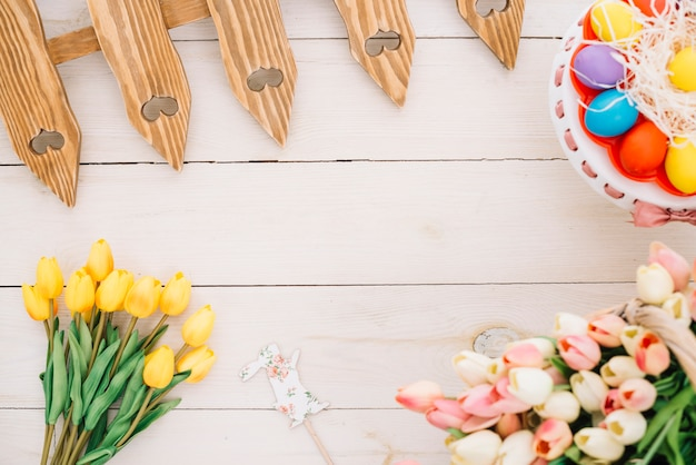 Easter prop; tulips; easter eggs; tulips and fence on wooden desk