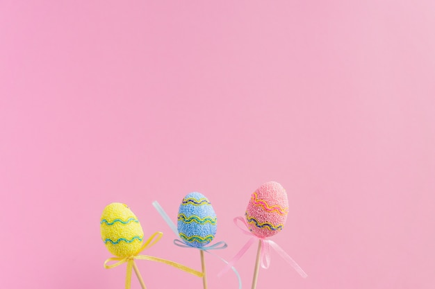 Easter purple, yellow and blue decorated eggs stand on a wooden sticks on pink background. minimal easter concept. happy easter card