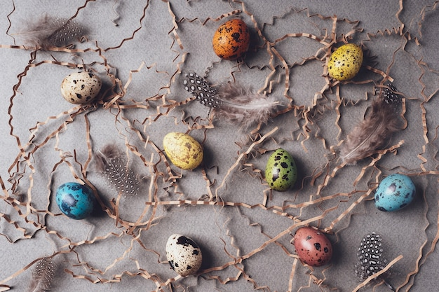 イースターウズラの卵、干し草、イースターバニー、羽、パターン。イースターの背景。灰色の背景、フラットレイ、上面図に着色された卵を描いた。