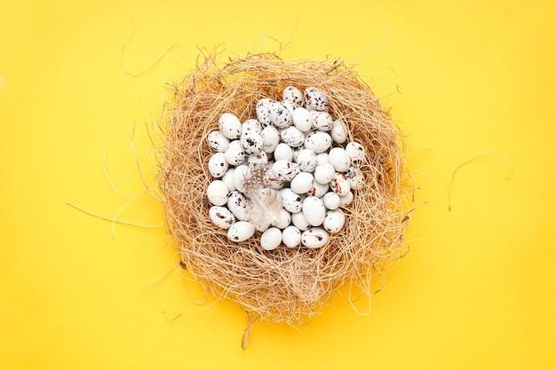 Пасхальные перепелиные яйца в гнезде на желтом