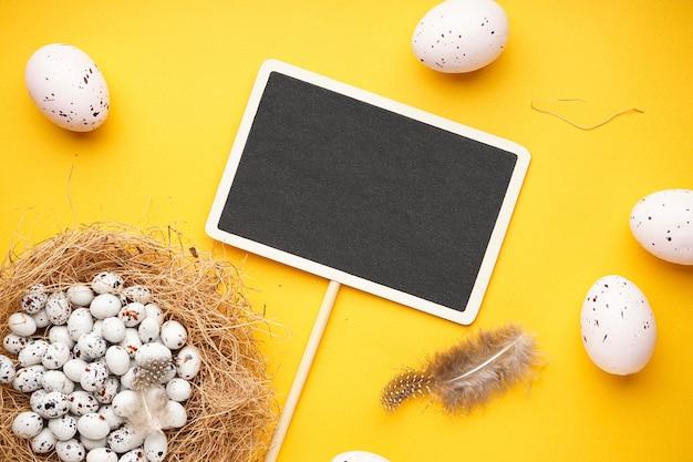 Пасхальные яйца в гнезде с пасхальными куриными яйцами и перьями на желтой поверхности. вид сверху.