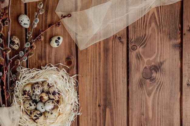 木製の背景、コピースペースの巣と柳の枝のイースターウズラの卵。
