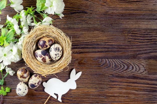 わらの巣と花の枝を持つ白いイースターバニーのイースターウズラの卵
