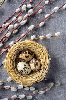 わらの巣と柳の枝のイースターウズラの卵、灰色のコンクリートの背景に柔らかいふわふわの銀色、テキストのコピースペース
