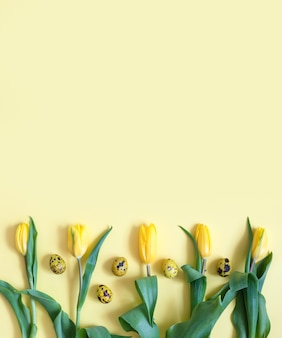 Easter quail eggs and tulips on a yellow background. easter border or frame. vertical orientation. copy space, top view, flat lay.
