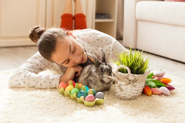 Easter rabbit in home with eggs and green grass
