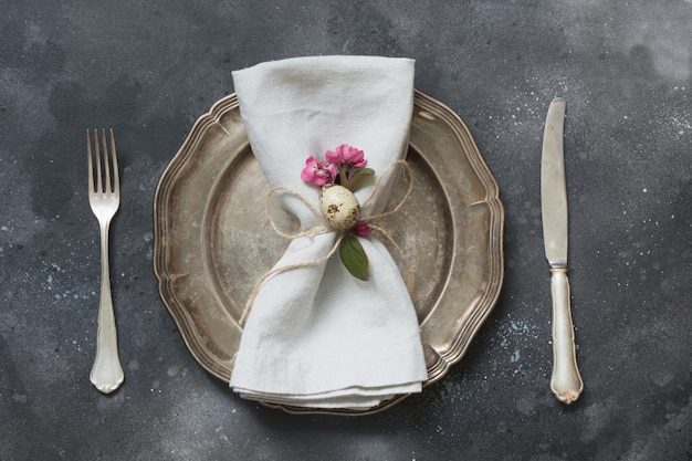 Easter romantic dinner. elegance table setting with spring pink flowers on dark. top view.
