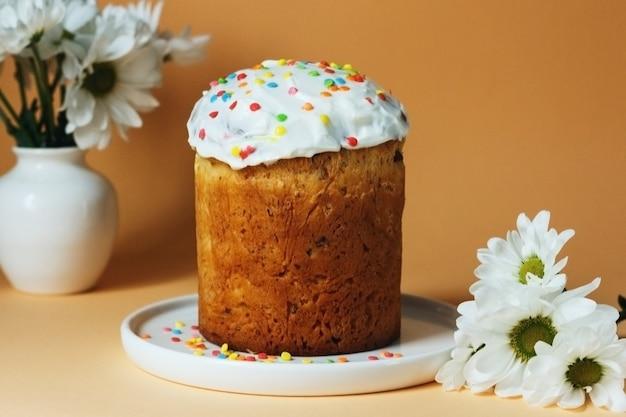 Пасхальный русский или украинский традиционный торт кулич с цветами вокруг на оранжевом фоне