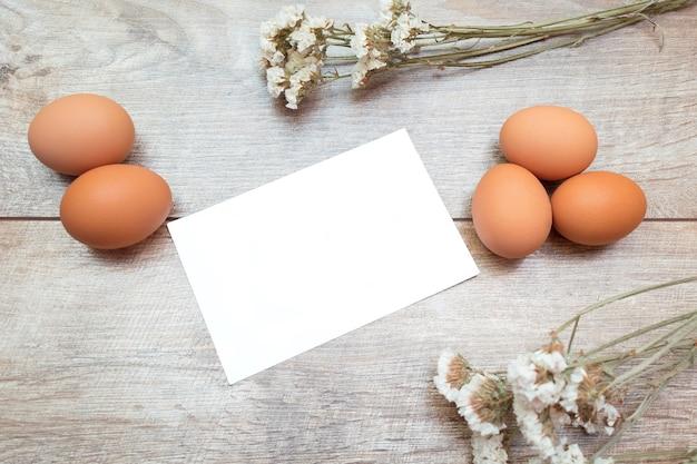 空白のグリーティングカード、鶏卵、茶色のテーブルに白い花とイースターの素朴な構成。