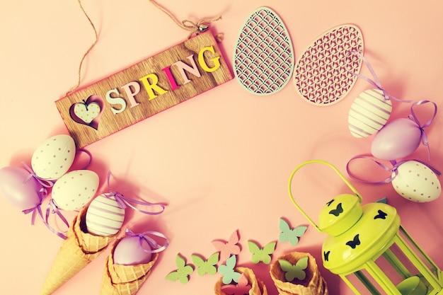 イースタースプリングコンセプト。イースターエッグとアイスクリームコーンのフラットレイまたはトップビュー。イースターや春の背景テキストのための場所。