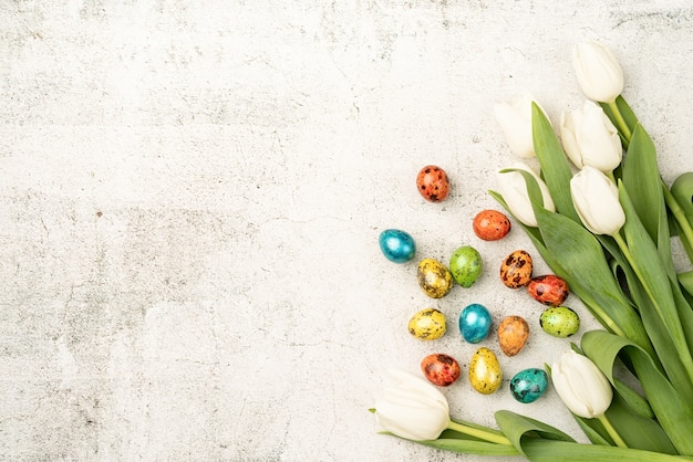 Easter and spring concept. top view of white tulips and colored easter eggs on concrete backgrund