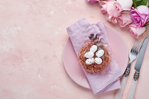 Сервировка стола приветствия весны пасхи украшенная с розами и гнездом с пасхальными яйцами на синем цветном фоне. вид сверху. место для текста.