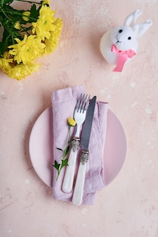 Сервировка стола приветствия весны пасхи украшенная желтыми хризантемами и милым кроликом на предпосылке розового цвета. вид сверху. место для текста.