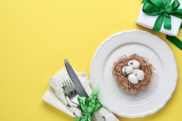 Сервировка стола приветствия весны пасхи с подарочной коробкой с зеленой лентой, яичками и сладостной морковью на желтой предпосылке цвета тенденции. вид сверху. место для текста.