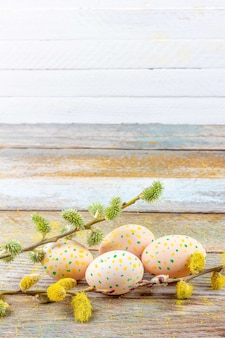 Easter spring still life of flowering willow branches and eggs on a retro wooden table on a white background