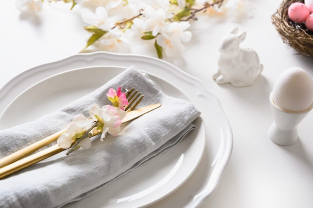 Easter spring table setting with blooming flowers on white table, christianity holiday.