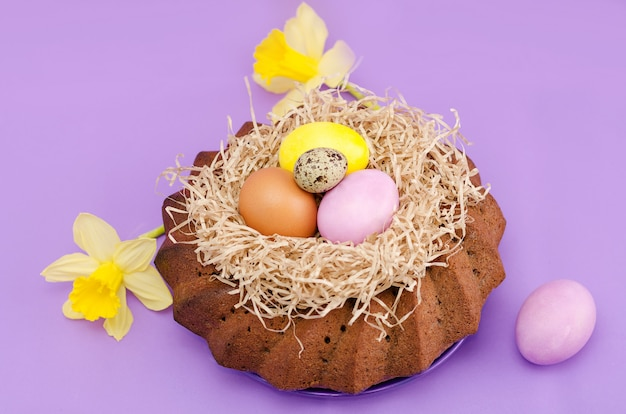 Easter still life, easter cake, chicken and quail eggs, on a violet  background.