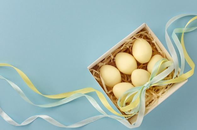 Пасхальный натюрморт. яйца из белого шоколада в коробке декорированы цветной лентой. скопируйте пространство.