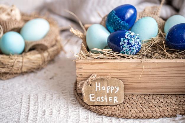 Natura morta di pasqua con uova blu, decorazioni per le vacanze.