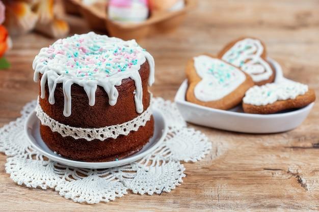 木製のテーブルにケーキと自家製クッキーのイースター静物。
