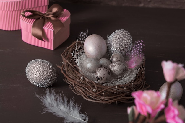 Пасхальный натюрморт с креативными пасхальными яйцами в гнезде и перьями в сдержанном ключе