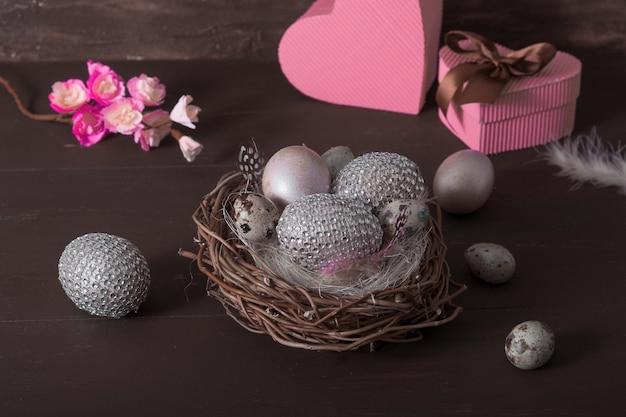 Пасхальный натюрморт с креативными пасхальными яйцами в гнезде в сдержанном ключе