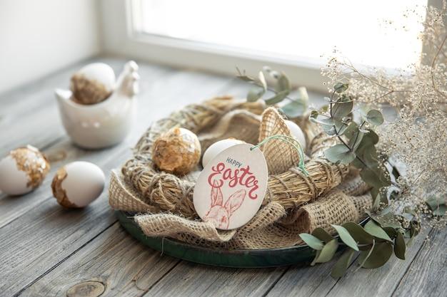 Пасхальный натюрморт с украшенными пасхальными яйцами и декоративным гнездом на деревянной поверхности. счастливой пасхи желает концепции.