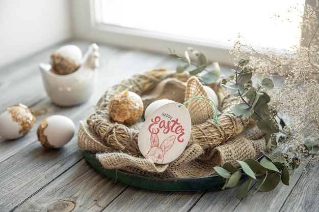 Easter still life with decorated easter eggs and decorative nest on a wooden surface. happy easter wishes concept.