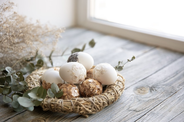 Easter still life with decorated easter eggs and decorative nest on a wooden surface with dry twigs.