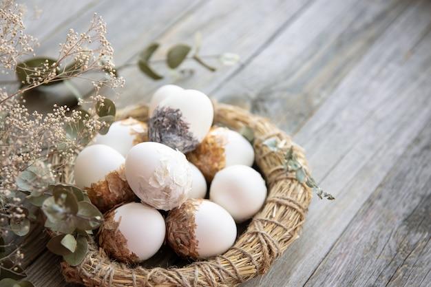 Natura morta di pasqua con uova di pasqua decorate e nido decorativo su una superficie di legno con ramoscelli asciutti