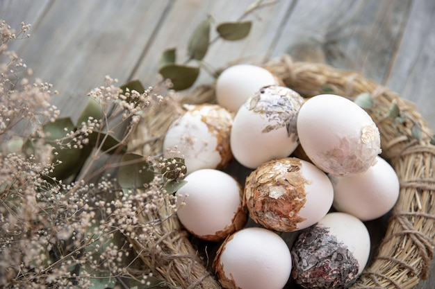 Easter still life with decorated easter eggs and decorative nest on a wooden surface with dry twigs