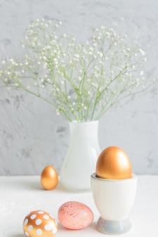 イースターの卵と灰色の背景に咲くカスミソウの花のある静物