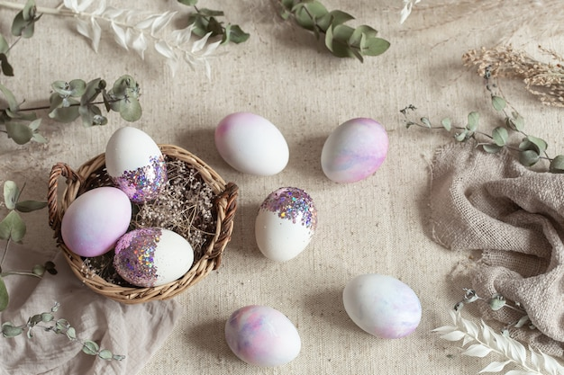 籐のかごにスパンコールで飾られた卵のイースター静物。ハッピーイースターのコンセプト