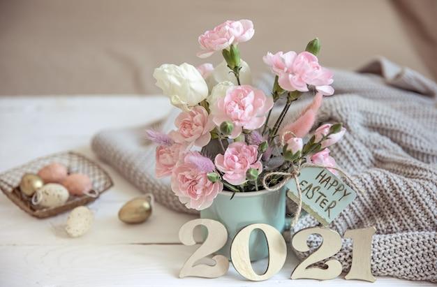 Natura morta pasquale con fiori freschi di primavera in un vaso, lavorata a maglia con un elemento e numero decorativo dell'anno 2021.