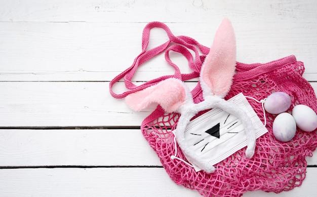 ピンクのストリングバッグ、装飾的なイースターバニーの耳、医療用マスク、木製の表面に卵があるイースターの静物。