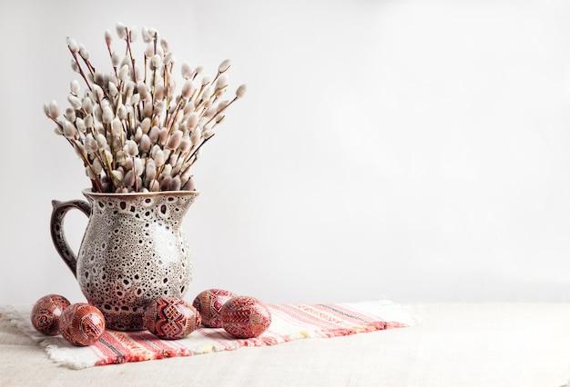 Пасхальный натюрморт с писанкой и ветвями ивы в керамическом кувшине на традиционной украинской ткани. украшенные пасхальные яйца, традиционные для культуры восточной европы