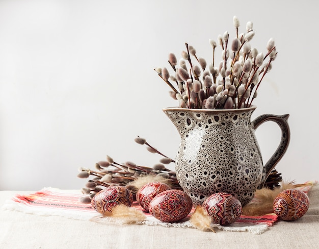 Easter still life with pysanka and willow branches in ceramic jug on traditional ukrainian cloth. decorated easter eggs, traditional for eastern europe culture