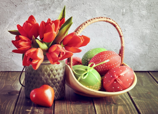 Easter still life with red tulips, wrapped gift and easter eggs
