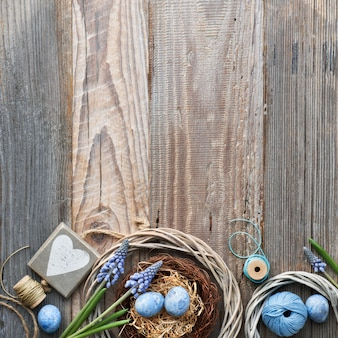 Easter surface with eggs, blue hyacinth flowers and  wooden heart, top view on rustic wood, copy-space