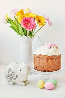 Easter sweet bread, easter cake and multi-colored eggs with tulips and a white rabbit.