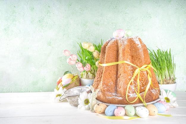 Пасхальные сладости и украшения фон, сладкий пасхальный кулич панеттоне с красочными крашеными яйцами, весенней травой и декором, копией пространства для текста