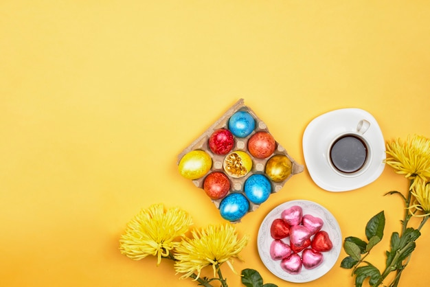 Easter sweets. bright yellow spring flowers, a coffee mug with sweets. decorated easter eggs on yellow background. easter morning
